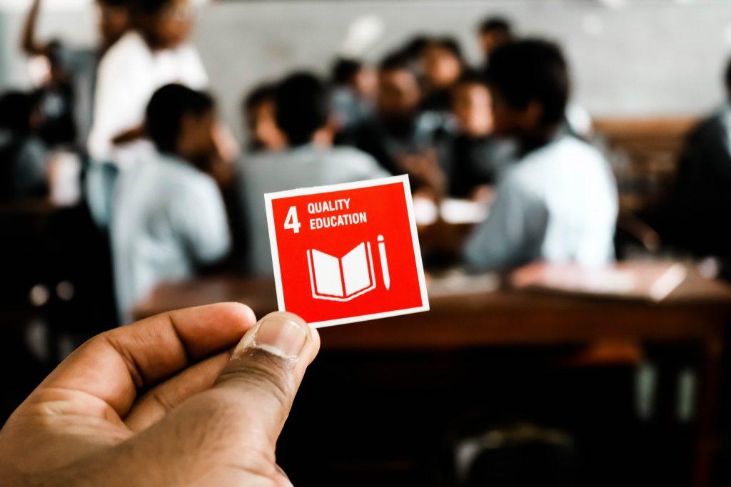 Foto de uma mão segurando um papel quadrado em que se encontra o Objetivo 4 (Educação de Qualidade). Ao fundo, é possível ver estudantes de costas para a câmera reunidos e conversando em uma sala de aula.
