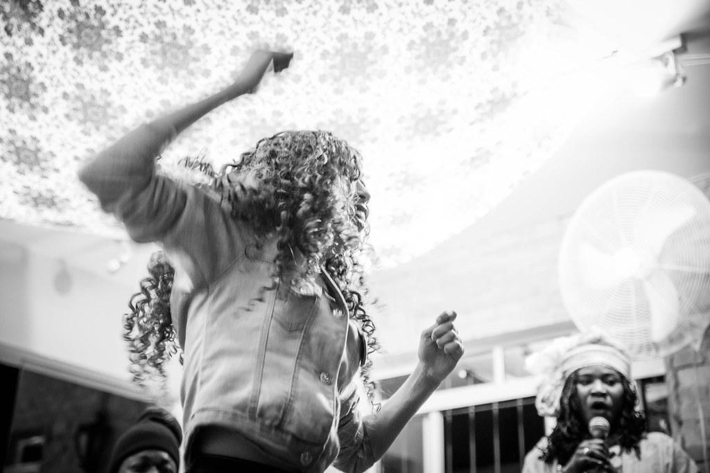 Uma fotografia em preto e branco de uma mulher negra dançando com os braços levantados. O ângulo da foto é de baixo para cima. No canto inferior esquerdo, ao fundo, uma mulher negra de turbante segura um microfone e canta.