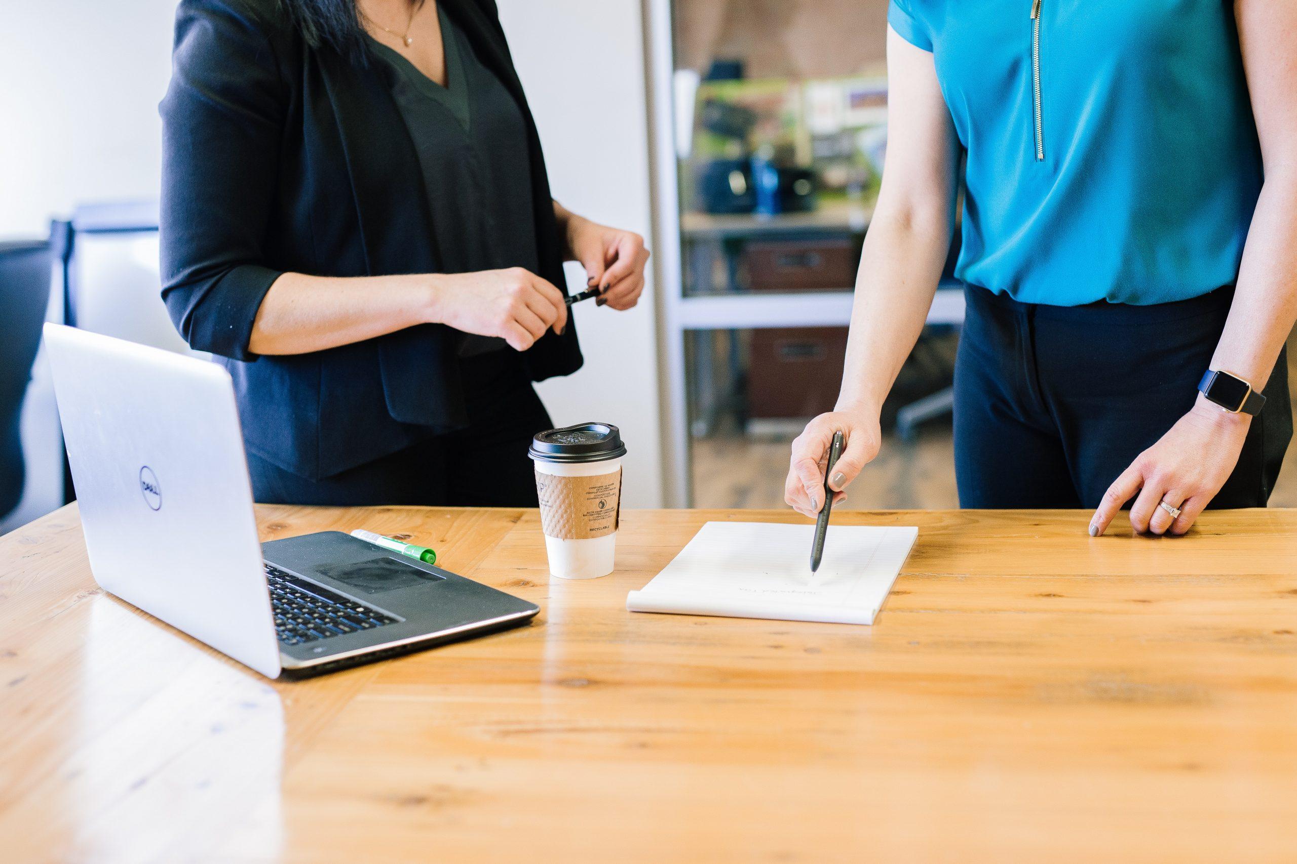 Fotografia de duas mulheres em um escritório com roupas sociais. A foto não mostra os rostos delas. Uma segura uma caneta, enquanto a outra aponta com uma caneta para um contrato. Em cima da mesa, há um copo de café e um notebook.
