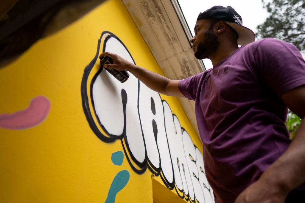 Fotografia de um homem segurando uma lata de tinta e desenhando um grafite na parede.