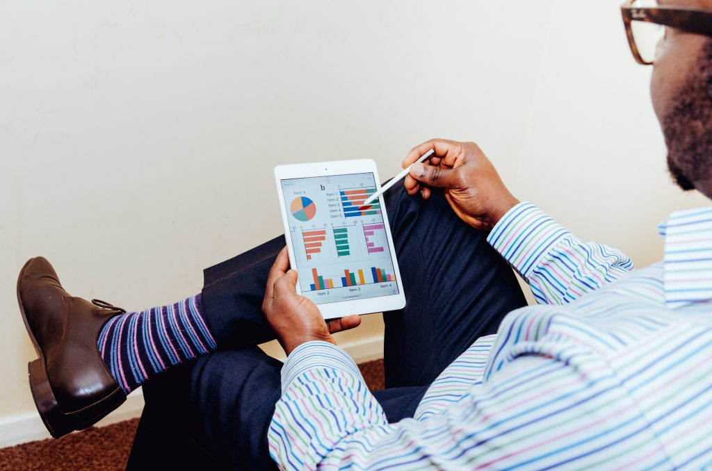Fotografia de um investidor de costas sentado e segurando um tablet. Ele aponta para a tela do aparelho, onde se vê diversos gráficos coloridos com o desempenho de empresas.