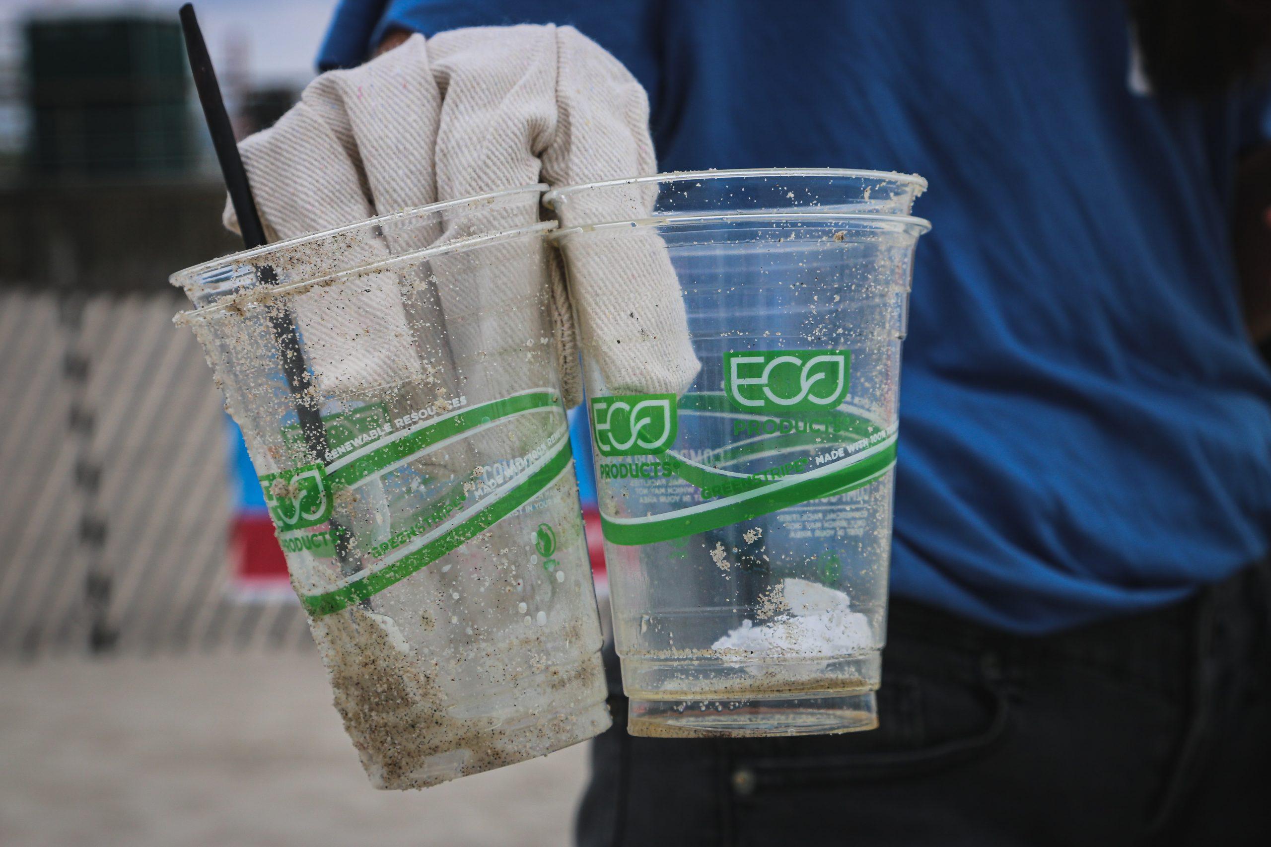 """Fotografia de uma mão, com luvas de coleta de lixo, segurando dois copos plásticos cobertos de areia da praia. Nos copos, lê-se """"eco"""" e há grafismos verdes que remetem à sustentabilidade."""