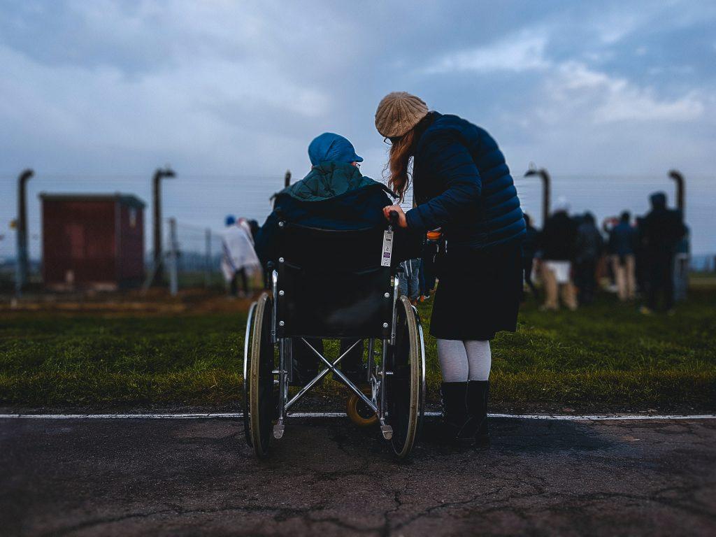 Fotografia de duas pessoas de costas. Uma é uma pessoa com deficiência, em uma cadeira de rodas, e outra é uma pessoa sem deficiência, ao lado dela. Ambas olham para o horizonte.
