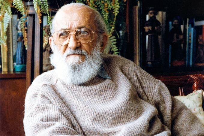 Fotografia de Paulo Freire, a cores. Ele está de óculos olhando para o lado.